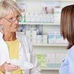 Senior female pharmacist giving prescribed medicine to customer in pharmacy